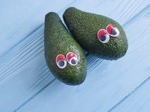 Шарж авокадоа наблюдает свежая на голубом деревянном витамине концепции Стоковое Изображение RF