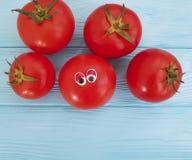 Шарж глаз томата смешной на голубой деревянной положительной эмоции Стоковые Фото