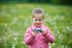 Шарж девушки наблюдая и игры играть на smartphone Стоковые Изображения RF