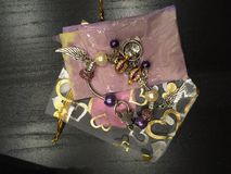 Шарики браслета, белых и фиолетовых с браслетом шармов Стоковая Фотография