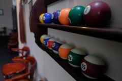 Шарики для биллиардов бассейна на шариках полки покрашенных или белых для биллиардов на деревянной предпосылке Стоковые Изображения