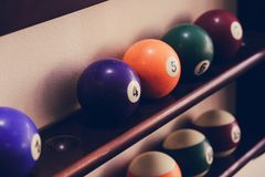 Шарики для биллиардов бассейна на шариках полки покрашенных или белых для биллиардов на деревянной предпосылке Стоковые Изображения RF