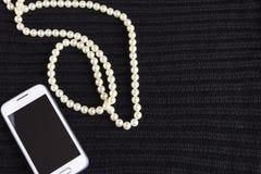 Шарики и телефон ` s женщин на черноте связали ткань стоковое изображение