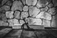 Шарики молитве с крестом на открытой старой книге на старом деревянном столе на предпосылке каменных стен Стоковые Фотографии RF
