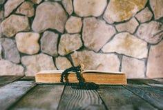 Шарики молитве с крестом на открытой старой книге на старом деревянном столе на предпосылке каменных стен Стоковое Изображение RF