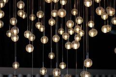 Шарики на люстре в lamplight, электрические лампочки вися от потолка, лампы освещения на темной предпосылке, селективной Стоковые Фотографии RF