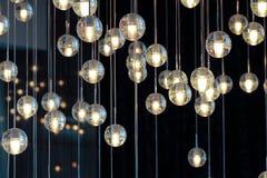 Шарики на люстре в lamplight, электрические лампочки вися от потолка, лампы освещения на темной предпосылке, селективной Стоковое Фото