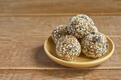 Шарики протеина сезама Oatsmeal Низко- жирные укусы энергии с овсяной кашей, чокнутым сезамом и черносливами на деревянной предпо стоковое изображение