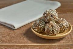 Шарики протеина сезама Oatsmeal Низко- жирные укусы энергии с овсяной кашей, чокнутым сезамом и черносливами на деревянной предпо стоковые фотографии rf