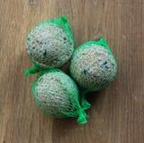 Шарики птицы тучные в зеленой сети на деревянной предпосылке стоковые фото
