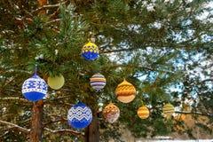 Шарики рождества вися на ветвях сосны покрытых с снегом Стоковые Фото