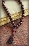 Шарики розария и святейшая библия на деревянной предпосылке Стоковое Изображение