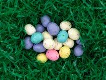 Шарики солода пасхального яйца в зеленой пластичной траве Стоковая Фотография