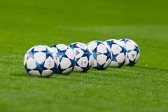 Шарики футбола лиги чемпионов в поле перед спичкой  Стоковые Фотографии RF