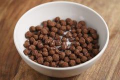 Шарики хлопьев шоколада с молоком в белом шаре для завтрака на деревянном столе Стоковые Изображения