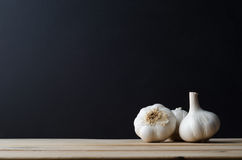Шарики чеснока аранжированные на древесине с черной предпосылкой Стоковая Фотография