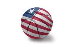 Шарик баскетбола с национальным флагом Либерии на белой предпосылке стоковое фото rf