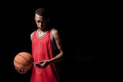 Шарик баскетбола в наушниках держа шарик и используя smartphone Стоковое Фото