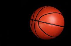 Шарик баскетбола над чернотой Стоковые Изображения