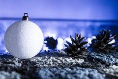 Шарик белого рождества с дисплеем конусов сосны зимним Стоковые Изображения