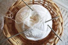 Шарик белых шерстей и вязать игл в плетеной корзине стоковая фотография rf