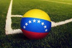 Шарик Венесуэлы на положении углового удара, предпосылке футбольного поля Национальная тема футбола на зеленой траве иллюстрация штока