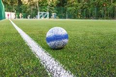 Шарик лежит около боковой линии футбольного поля с искусственным концом-вверх дерновины Стоковые Изображения