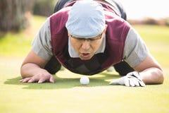 Шарик игрока в гольф дуя в отверстии Стоковая Фотография