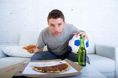 Шарик и пивная бутылка молодого человека один держа смотря футбольную игру на кресле софы телевидения дома Стоковые Изображения RF