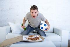Шарик и пивная бутылка молодого человека один держа смотря футбольную игру на кресле софы телевидения дома Стоковое фото RF