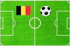 Шарик и флаг Бельгии на предпосылке футбольного поля Стоковые Фото