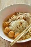 Шарик креветки отбензинивания вермишели риса и кипеть куском свинина в супе едят деревянной палочкой Стоковые Фото