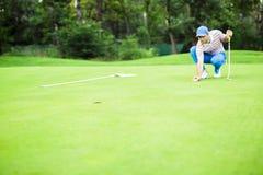 Шарик маркировки игрока гольфа на зеленом цвете установки Стоковые Изображения