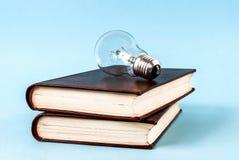 Шарик на 2 закрытых книгах изолированных на голубой предпосылке Стоковое Изображение RF