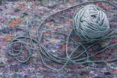 Шарик покрашенной веревочки на предпосылке ткани стоковое изображение