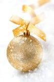 Шарик рождества золота в падая снежке стоковое изображение