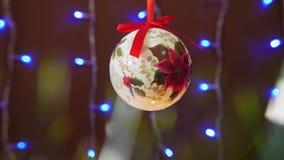 Шарик рождества с красной лентой с светящей гирляндой на заднем плане видеоматериал