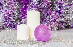 Шарик рождества сирени, 2 белых свечи и шарики Стоковое Фото