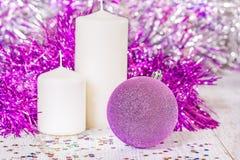 Шарик рождества сирени и 2 белых свечи Стоковые Фото