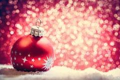 Шарик рождества стеклянный в снеге предпосылка яркого блеска стоковые фото