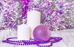 Шарик рождества, шарики и 2 белых свечи Стоковые Фото