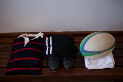 Шарик рэгби с одеждами и ботинками на деревянной скамье Стоковые Фотографии RF