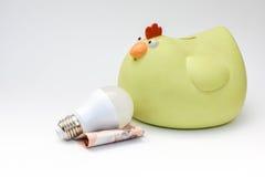 Шарик СИД и желтая копилка цыпленка Стоковая Фотография