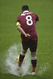 Шарик стрельбы футболиста на затопленном поле Стоковые Фото