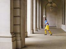 Шарик футболиста отскакивая с головы в портике Стоковые Изображения RF