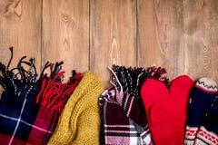 Шарфы и mittens уютной предпосылки зимы теплые связанные на деревянной предпосылке с космосом для взгляд сверху текста скопируйте Стоковые Изображения