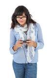 Шарф и стекла молодой женщины нося играя видеоигры Стоковая Фотография