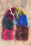 Шарф меха радуги против деревенской предпосылки с рожками оленей стоковые изображения