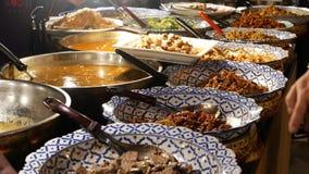 Шары с различными азиатскими блюдами на стойле Шары сортированных традиционных тайских блюд помещенных на стойле обедающего улицы акции видеоматериалы