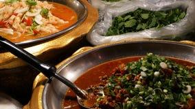 Шары с различными азиатскими блюдами на стойле Шары сортированных традиционных тайских блюд помещенных на стойле обедающего улицы сток-видео